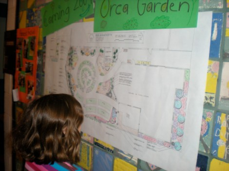 An Orca student looking at the new garden design that is posted in the hallway.